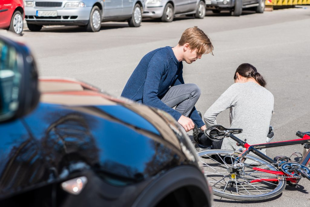 man helping woman involved in a bicycle accident